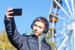 A teenager in a black jacket listens to music on headphones and makes selfie on the background of a Ferris wheel on a sunny autumn. Autumn. A teenager in a black Royalty Free Stock Images