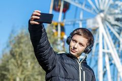 Autumn. A teenager in a black jacket listens to music on headphones and makes selfie on the background of a Ferris wheel on a sunn. A teenager in a black jacket Stock Photo