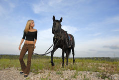 Teenager and black stallion Royalty Free Stock Image