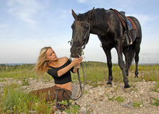 Teenager and black stallion in nature Royalty Free Stock Images