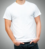 Teenager With Blank White Shirt. White t-shirt on a young man template on gray background Stock Images