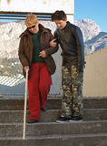 A teenager and a blind woman. Teenager helping (holding under his arm) a blind woman (with a white stick and black sunglasses) to walk down the stairs. Vertical Stock Photos