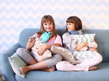Teenager blond sister in pajamas on the sofa. Two happy teenager blond sister in pajamas on the sofa with pillows in the cozy design bedroom interior Stock Images
