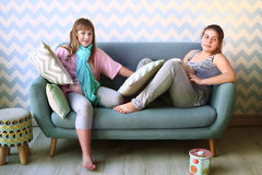 teenager blond sister in pajamas on the sofa Stock Photo