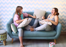 Teenager blond sister in pajamas on the sofa Stock Photos