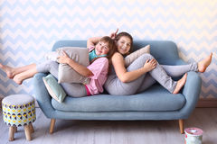 Teenager blond sister in pajamas on the sofa Royalty Free Stock Images