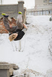 Teenager blonde hair guy training parkour jump flip in the snow covered park Royalty Free Stock Image