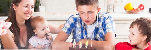 Teenager blows out the candles on a birthday cake. Big happy family happily celebrate the birthday of the son of a teenager. make a wish stock photos