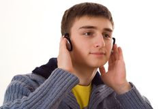 Teenager in a blue blouse with headphones on white Stock Images