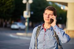 A teenager talking on his phone while walking around the city on the background of the street. A teenager in a blue shirt with a backpack on his back is talking Stock Image