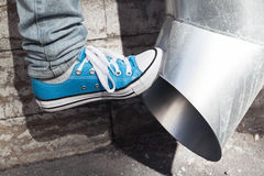 Teenager in blue sneakers kicks drainpipe Stock Photos