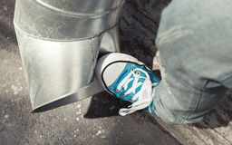 Teenager in blue sneakers kicks drainpipe, aggression Stock Images