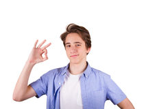 Teenager in blue T-shirt. Happy teenager gesturing OK sign and smiling. Student in blue shirt, isolated on white background Stock Image