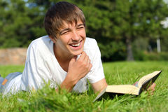 Teenager with a book. The teenager reads the book on a summer meadow Royalty Free Stock Image
