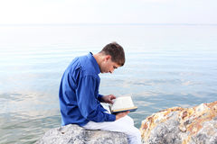 Teenager with book. Teenager sitting with a book near the water Royalty Free Stock Photo