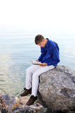 Teenager with book. Happy teenager sitting with a book on the stone on the seaside Royalty Free Stock Photography