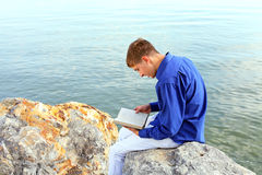 Teenager with book. Happy teenager sitting with a book on the stone on the seaside Stock Photos