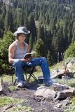Teenager with  book in mountain hike. Teenager close to camp-fire with kebab and book in mountain hike Stock Image