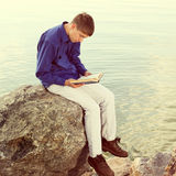 Teenager with a Book outdoor. Toned photo of Teenager reading a Book near the Water Stock Images