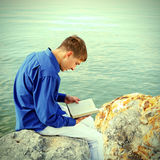 Teenager with a Book outdoor. Toned photo of Teenager reading a Book near the Water Royalty Free Stock Photography