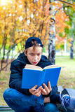 Teenager with the Book. Teenager read the Book in the Autumn Park Royalty Free Stock Photography