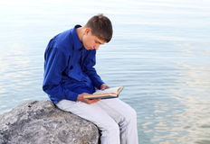 Teenager with a Book. Sit on the Stone at the Seaside Royalty Free Stock Photography