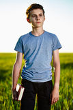 Teenager with a book in a wheat field. Portrait of a teenager boy with a book in a wheat field at sunset Royalty Free Stock Images