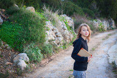 Teenager with books. Girl carrying books, walking in the countryside Stock Images
