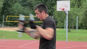 Teenager boxing with dumbbells on sports ground stock video footage