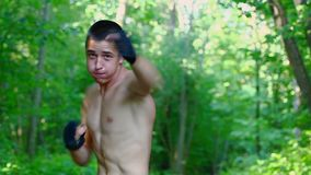 Teenager boxing in the park stock video