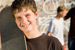 Teenager boy. Young teenager boy holding a skateboard with friends in the background stock photography