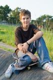 Teenager boy. Portrait of teenager boy sitting on skateboard Royalty Free Stock Photography