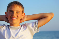 Teenager boy against sea, hands behind head Royalty Free Stock Photos