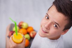 Teenager boy with all the right diet choices - holding fruit plate and fresh juice stock photos