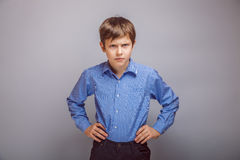 Teenager boy angry hands on hips gray background Royalty Free Stock Photography