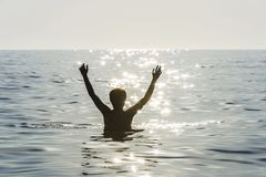 Teenager boy bathing in the sea with his arms raised royalty free stock photography