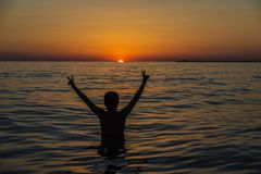 Teenager boy bathing in the sea at sunset in Sicily stock photo