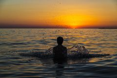 Teenager boy bathing in the sea at sunset in Sicily. Silhouette of a teenager boy playing to throw water into the air on a beach at sunset in summer in Sicily stock photos