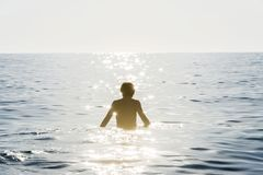 Teenager boy bathing in the sea surrounded by sunbeam reflection stock image