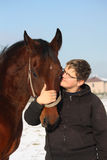 Teenager boy and bay horse portrait in winter Stock Photography