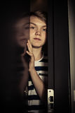 Teenager boy behind ajar door Stock Images