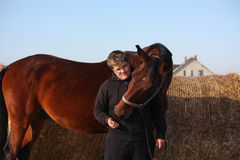 Teenager boy in black hugging brown horse Stock Photo