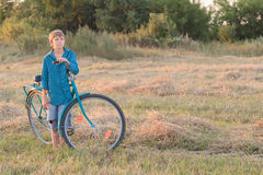 Teenager boy with blue bike in farm field Stock Images