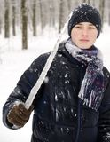 Teenager boy in a blue jacket, in a checkered scarf and in a dark blue hat with a icicle in his hands. Against the backdrop of the winter forest Stock Photo