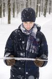 Teenager boy in a blue jacket, in a checkered scarf and in a dark blue hat with a icicle in his hands. Against the backdrop of the winter forest Stock Photography