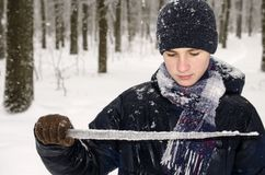 Teenager boy in a blue jacket, in a checkered scarf and in a dark blue hat with a icicle in his hands. Against the backdrop of the winter forest Royalty Free Stock Photography