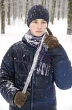 Teenager boy in a blue jacket, in a checkered scarf and in a dark blue hat with a icicle in his hands. Against the backdrop of the winter forest Royalty Free Stock Photo