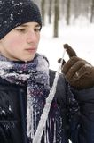 Teenager boy in a blue jacket, in a checkered scarf and in a dark blue hat with a icicle in his hands. Against the backdrop of the winter forest Stock Photos