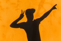 Teenager Body Hands Sign Shadow Wall. Teenager boy body profile hat with hands sign shadow on yellow textured wall abstract concept stock photos