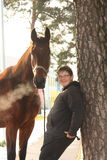 Teenager boy and brown horse standing near the tree Stock Photos